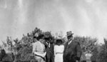 Elderly man, middle-aged couple and young lady posed against trees