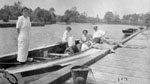 Three women and man in row boat