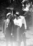 Two men and a woman standing in garden