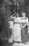 Two young women standing in garden