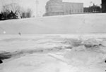 Ice-covered 16 mile creek with Commercial hotel in background.