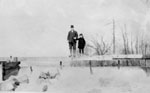 Man and girl on top board of mill pond spillway.