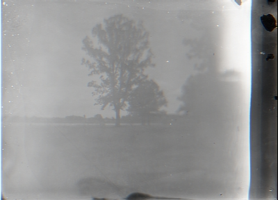 Very Faded View of a Field with a Lake or River in the Background