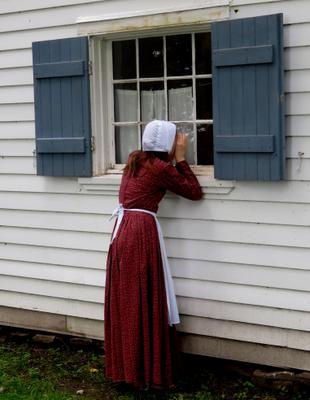 Girl peeks through Thomas House Window
