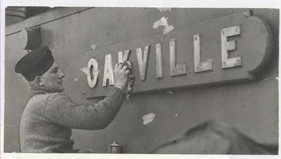 HMCS Oakville sailor cleans nameplate