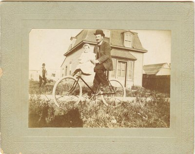 Photograph of a man on bicycle with a child