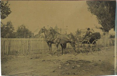 Tintype of a man in a buggy with a child