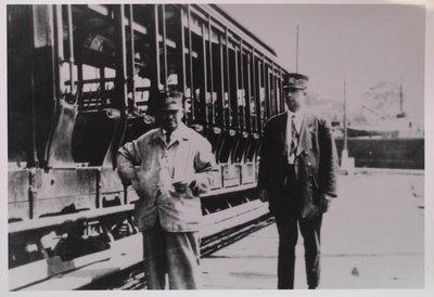 Two Rail Workers in Front of an Open Side Car