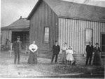 Men, Women and Child in Front of Building