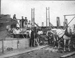 Men and a horse at a building constructing