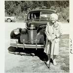 Photograph of Woman in front of vehicle