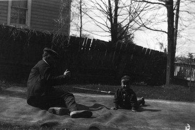 Ewan Macdonald on lawn with Stuart, ca.1920.  Leaskdale, ON.
