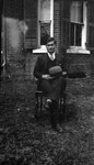 Chester with hat on knee sitting in garden, Norval, ON.