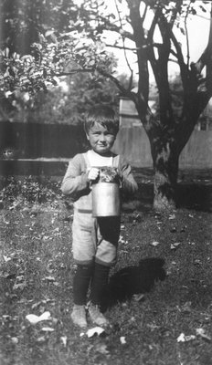 Stuart with Paddy the cat in bucket, age 5 1/2 years, ca.1921.  Leaskdale, ON.