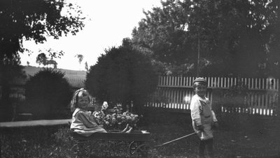 Stuart pulling Ruth Cook in wagon, ca.1919.  Leaskdale, ON.