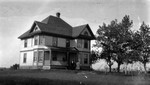 Three (unidentified) figures in front of house, PEI.