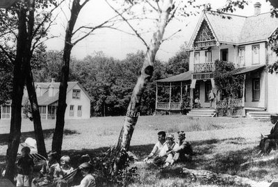 Children and youth on lawn, and Lucy Maud Montgomery on veranda in background