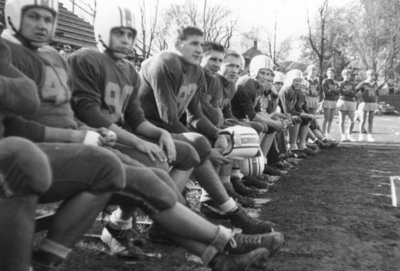 Waterloo College football players sitting on a bench