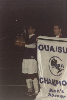 Wilfrid Laurier University men's soccer players with OUA banner and trophy