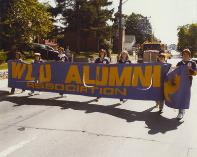 Wilfrid Laurier University students carrying banner during parade