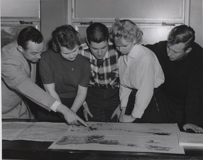 Ralph Krueger and students looking at a map