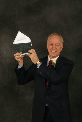 Paul Heinbecker holding Alumnus of the Year award