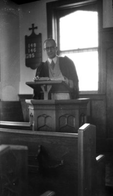 Earle Shelley standing at podium in chapel