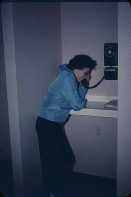 Woman using the telephone in Conrad Hall, Waterloo Lutheran University