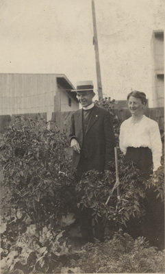 Rev. Charles G. Beck and Mrs. Beck standing in garden