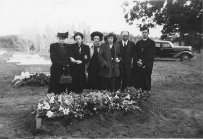 Five people and a pastor in a cemetery