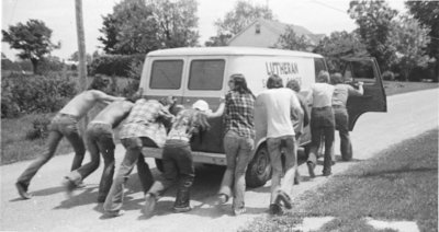 People pushing the Lutheran Summer Camps van