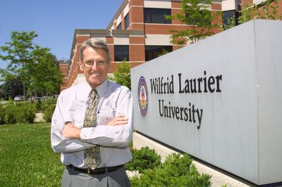 Lyle S. Hallman in front of Laurier sign, 2002
