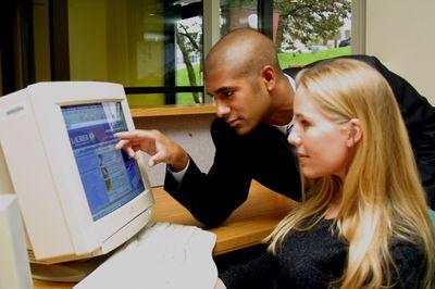 Students examining computer monitor