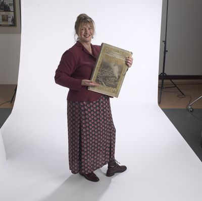 Virginia McKendry holding Brantford Expositor newspaper, 2002
