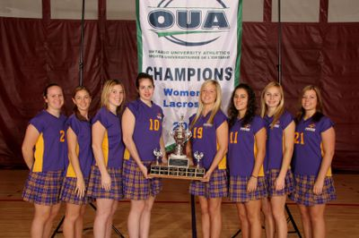 Women's lacrosse team with championship banner and trophy, 2006