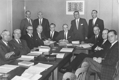 Thirteen men in a meeting room