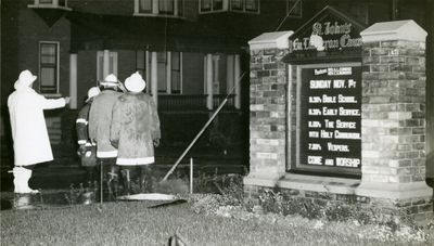Fire fighters standing in front of St. John's Lutheran Church sign during fire