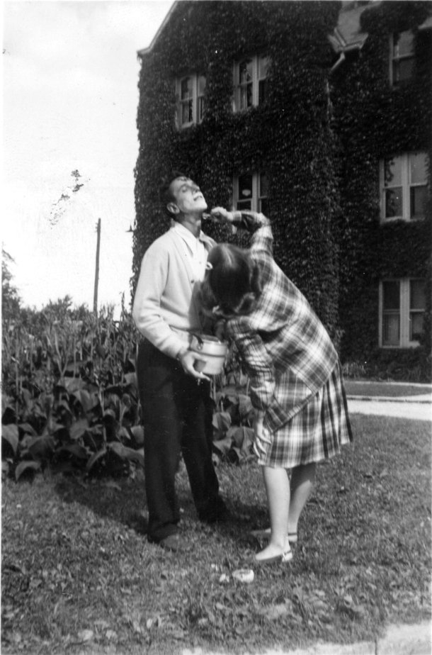 Woman shaving a man's face