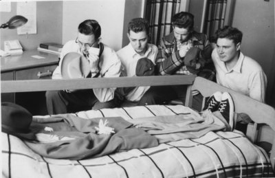 Waterloo College students gathered around a dormitory bed
