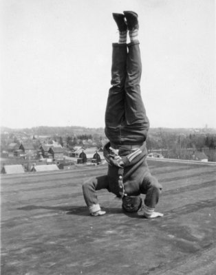 Waterloo College student doing a headstand on the roof of Willison Hall