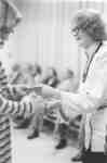 Flora Roy shaking hands with unidentified woman