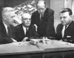 Four men looking at model of Waterloo Lutheran Seminary building