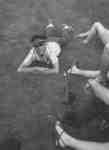 Male Waterloo Lutheran University student laying on grass