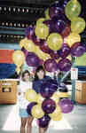 Two women holding purple and yellow balloons