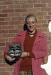 Woman holding football helmet