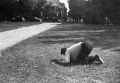Man kneeling on lawn at Waterloo College