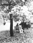 Two students sitting on a bench at Wilfrid Laurier University