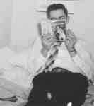 Man reading a book and smoking a cigarette