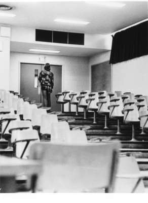 Man walking up stairs of empty lecture hall
