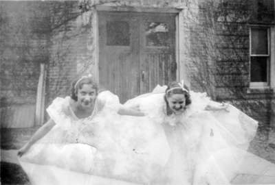 Two young women in formal gowns, in front of Willison Hall